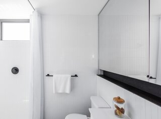 The simple material palette extends to the bathroom.
