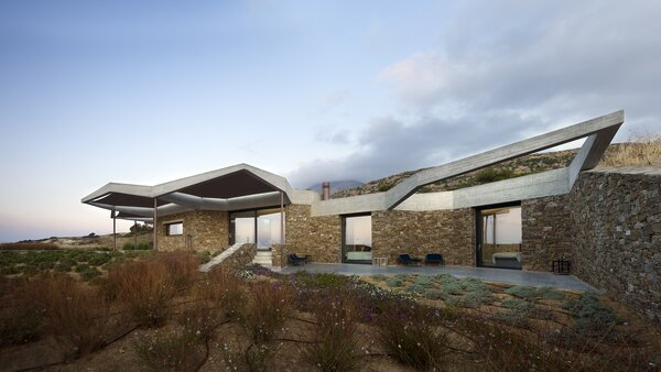 The exposed concrete framework cantilevers dramatically from the stone walls.