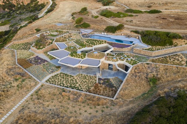 Each cell denotes a different area inside the house below it and is planted with a different species of aromatic plant from which essential oils can be extracted. The landscaped roof also helps to insulate the home and blend it into the environment.