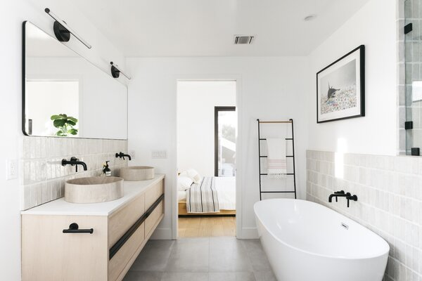 """The new bathroom has Cle tile and custom limestone sinks that Emily found in a chance search online. """"Marblebasinhub.com. They have incredible, incredible sinks,"""" she says."""