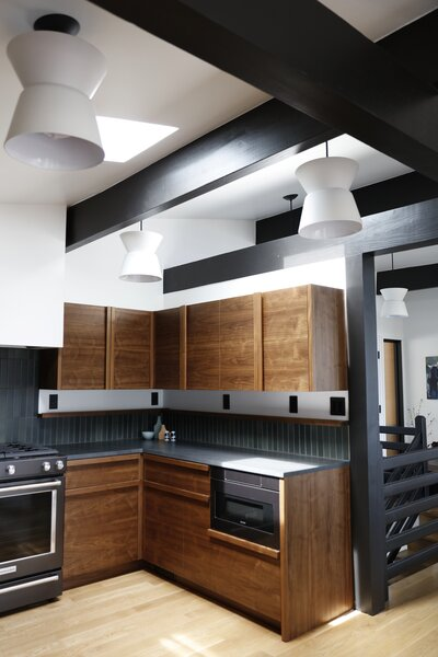 Light spills down over the exposed framework, and period lighting adds character. The counters are Black Vermont from Bedrosian in a leather finish, and the tile is Forest field tile from Heath.