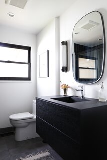A floating vanity saves space in the petite footprint. Cement tile covers the floor.