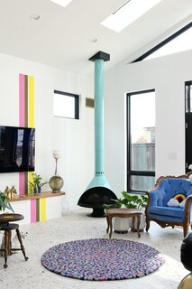 "An aqua Malm fireplace warms up a corner. The pink, green, and yellow stripes now reach the skylights and extend over an integrated storage space to the floor. ""My husband and I, we both actually hate having a TV visible to guests, but it's a necessary evil,"" says Shawn. ""So how do you make that interesting and without it being too busy? [The rainbow stripe] creates an element that draws your eye away."""