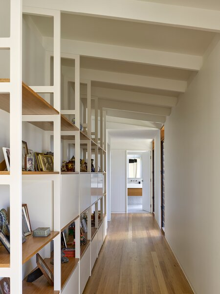 A long, airy hallway lines the guest wing with built-in shelves along the wall and a bathroom at the end of the corridor. The wing can be closed up seasonally when visitors aren't around as often.