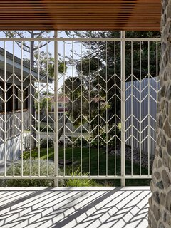 The decorative screen casts playful shadows across the front terrace.