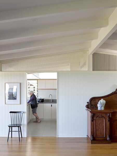 The kitchen was relocated to give the living area more breathing room. A slat detail above the beams bring attention to the preserved roof structure.