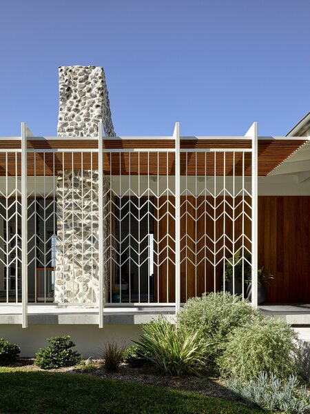 """Now, decorative screens """"provide dappled western shade and frame the view of the monumental chimney from the street,"""" says the firm."""