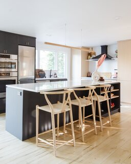 "The kitchen island is nine-and-a-half feet long, made possible by knocking down non-load-bearing walls and enlarging the room's footprint. The island is ""much larger than what most people would do in that space, because it's not that large of a space, but knocking down those walls and going with a large island makes the kitchen feel a lot more grand,"" says Devlin."