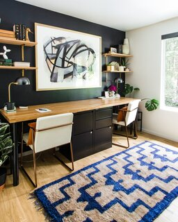 A dramatic black-painted wall is a backdrop for the home office. The renovation has compelled the couple to move into the home full-time and rent their Seattle townhome.