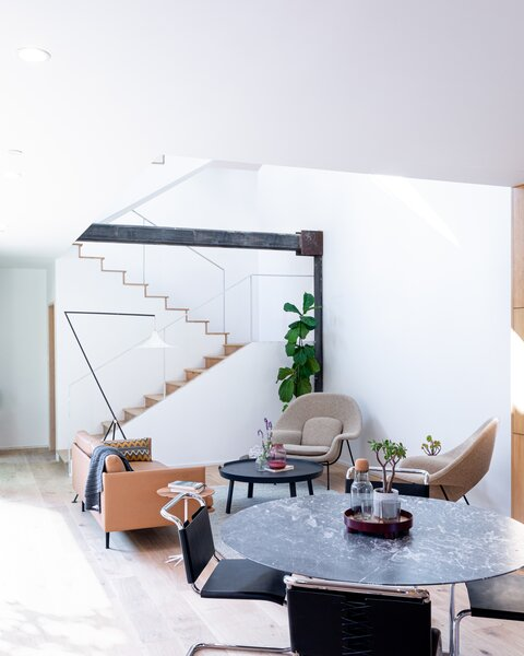 The living room is a double-height volume filled with natural light. The furniture and housewares are by Knoll and Muuto.