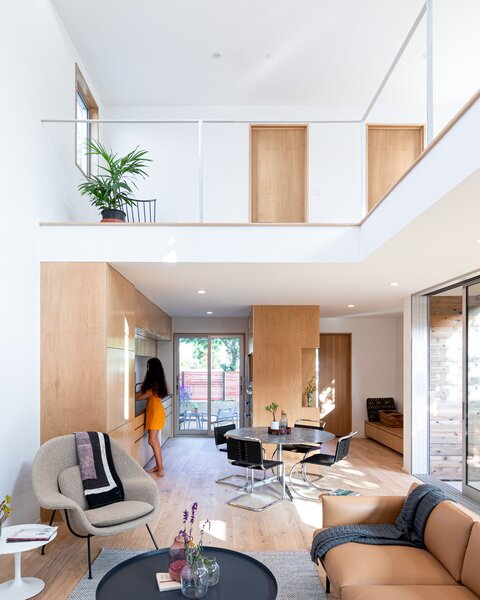 The mezzanine level hosts the bedrooms and overlooks the lower living spaces.