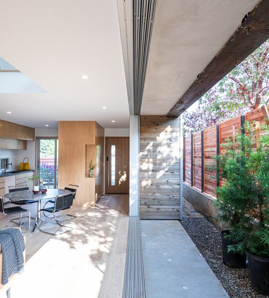 exposed steel structural elements and cedar siding meet in the side patio where 27 foot wide doors merge inside and out by enlarging the side yard beyond setback requirements saez pedraja made the house more narrow but by making it more narrow we made the