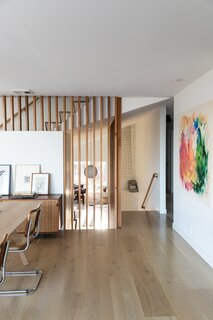 The new stair configuration creates a circulation core. A custom red-cedar screen knits the floors together.