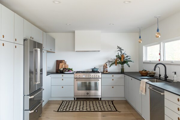 The kitchen layout was reconfigured so that the focus is on the view—the wall of windows, which look out on the ocean, is now underscored by one long, uncluttered counter. There, the faucet is Delta and the dishwasher is Bosch. The range stayed in nearly the same spot, and the opposite wall has been thickened with storage and the refrigerator column. Both the refrigerator and range are by Bertazzoni.