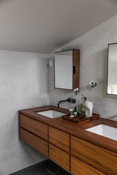 The new custom teak vanity and tub surround were designed by Jocie and fabricated by O'Brien Wood & Iron. At the vanity, Kohler sinks are joined with California faucets and medicine cabinets by Urban Outfitters. The vase is from Summer School.