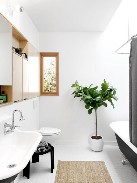 A claw-foot tub is combined with a wall-hung sink and a contemporary medicine cabinet by Kerf, continuing the tension between old and new. A new skylight brings in plenty of sunlight.