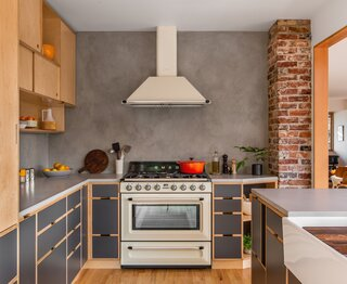 The preserved brick chimney was exposed and cleaned up in the remodel. A classic Smeg range and exhaust hood create a pleasing contrast with the contemporary Kerf cabinetry.