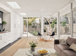 Floor-to-ceiling glass melds the tiny building with its surroundings, while nine-foot-tall ceilings give it a spacious feel.