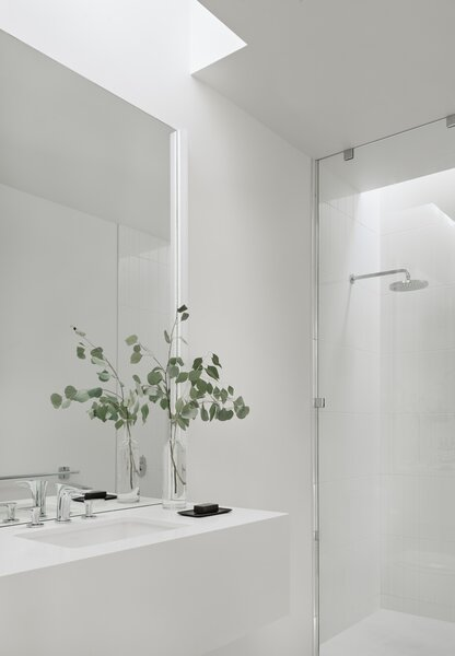 In the full bathroom, Caesartone forms the floating vanity for the sink, while the shower is covered in bright white 3x12 ceramic tile. The skylights make it so the lights aren't needed during the day.