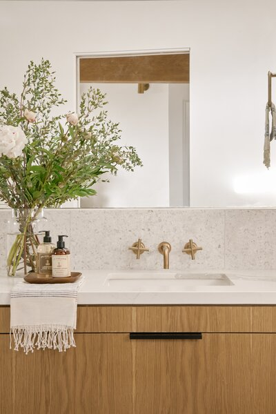 A terrazzo tile backsplash provides a lightly textured backdrop for the brass faucet and warm wood cabinetry.