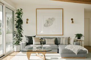 The living room made cozy with new furnishings. Brass Shaded Sconces from Onefortythree flank a painting by Nina Lance from Saatchi Art. The Rove Concepts Noah Sectional sits atop the Kailee Handwoven Wool Rug from Pottery Barn.