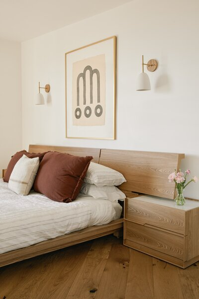 The Hunter bed and nightstands from Rove Concepts are positioned below the Leyland Sconce by Worley's Lighting.