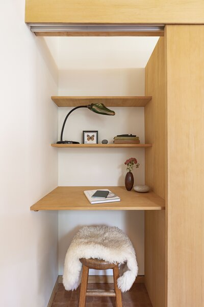 An office nook is tucked behind sliding doors in the bedroom closet.
