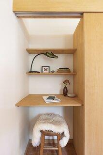 An office nook is tucked behind sliding doors in the bedroom closet.