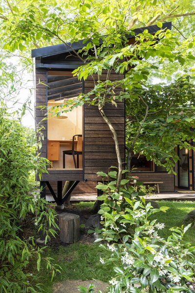 The tree house is just big enough for a desk and a chair, with a generous window looking into the leaves.