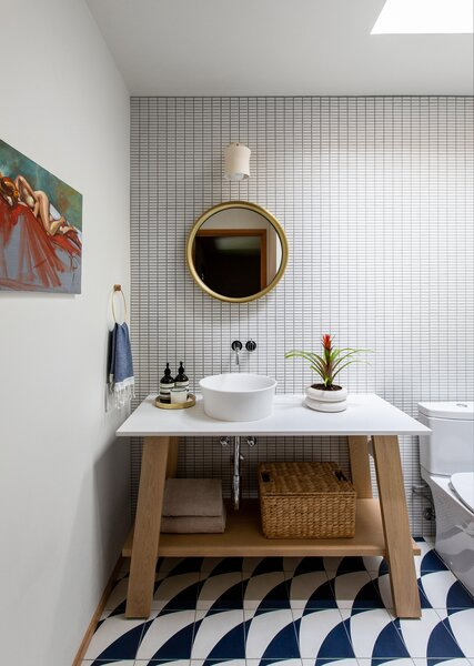 The guest bath features punchy Clé tile flooring and a mirror and sconce from Schoolhouse Electric.