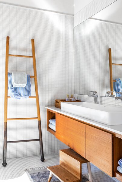 In the kids' bath, a custom vanity by Christopher Derek Bruno and a ladder by Lostine extend the home's warm material palette.
