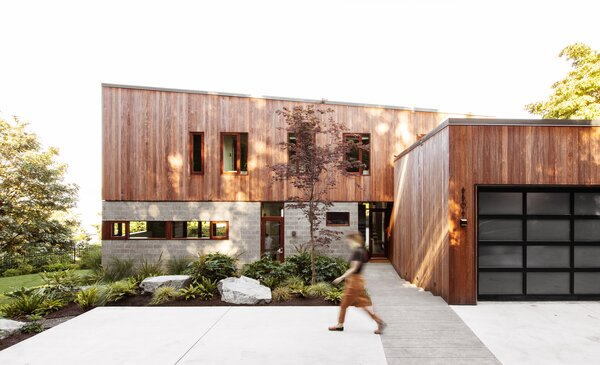 On the front facade, ground-faced concrete blocks contrast with cumaru wood tongue-and-groove siding.