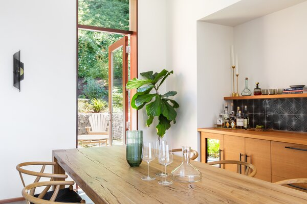 In the dining room, which leads to the sunken courtyard out front, a Restoration Hardware table is surrounded by Hans Wegner chairs. Fireclay Tile lines the backsplash above the sideboard.