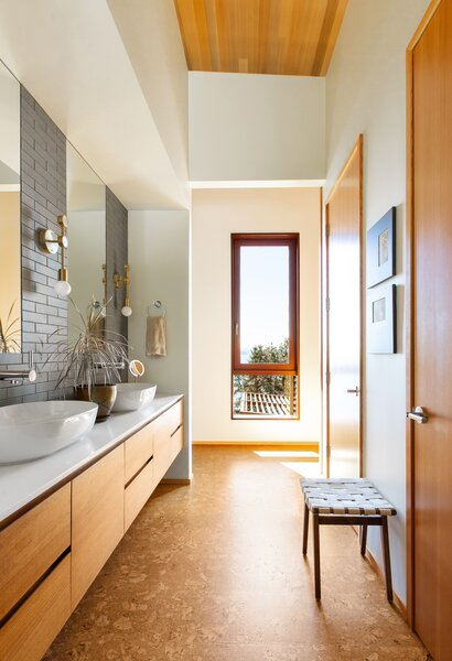 Cork flooring by Expanko runs from the bathroom to the hallway, mirroring the tones of the cedar ceilings. Heath Ceramics tile clads the vanity wall.