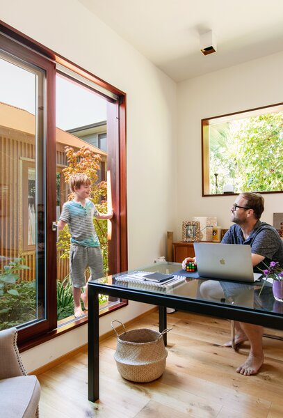 Large windows in the office help create the couple's desired effect of permeability throughout the home.