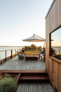 The roof deck, anchored by a gas fire pit from Paloform, boasts an incredible view of the water.