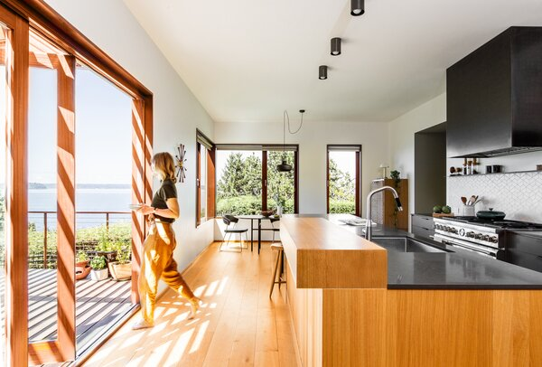 Duchateau engineered hardwood oak complements the kitchen's warm wood cabinetry. A broad sliding door connects the space to the outdoor deck, which spills down to the backyard.