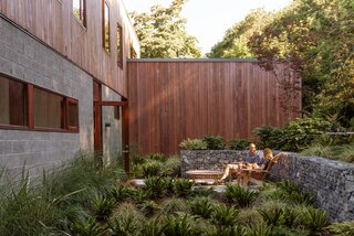 A sunken courtyard at the front of the home provides a private lounge space that connects to the dining room.
