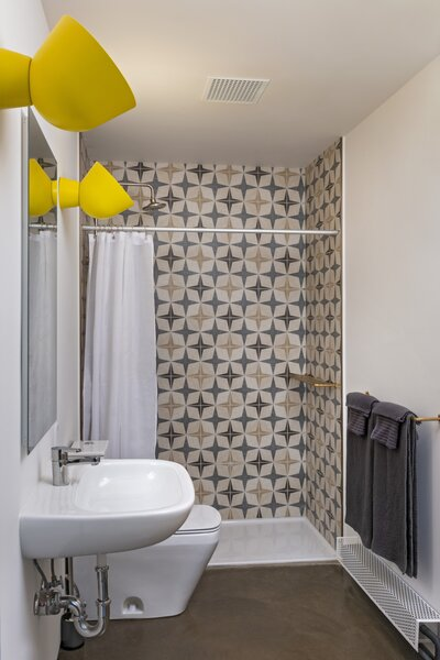 Ali chose a wall tile that reflects the early '70s era when the building was constructed. The oversized yellow wall lights are from IKEA.