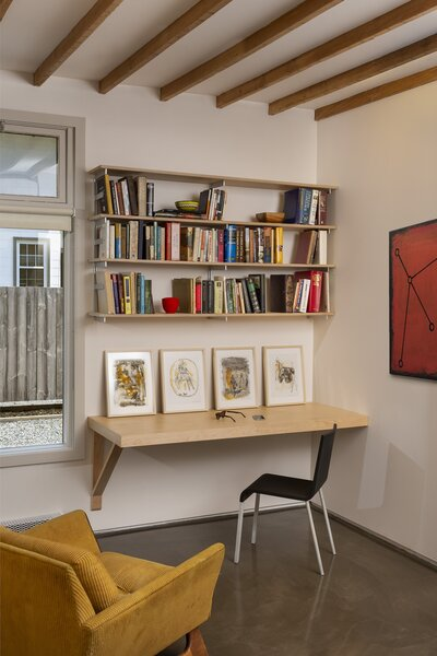 Ali's artworks line the studio desk and a painting by his son decorates the wall.