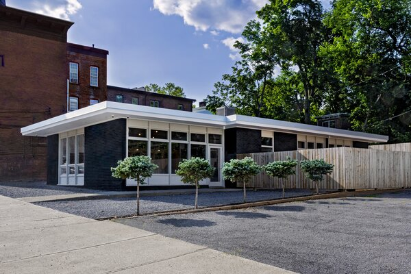 """The brick shell of the 1,863-square-foot building was painted matte black, which """"makes the roof float in a wonderful way and accentuates the white framing of the windows,"""" says Ali."""