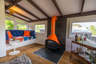 """With the porch enclosed, a built-in couch is a cozy spot next to the vintage stove, which is set on a slate hearth. """"I wanted the home to be cheerful and colorful,"""" says Azin, """"and used primary colors to enliven it."""""""