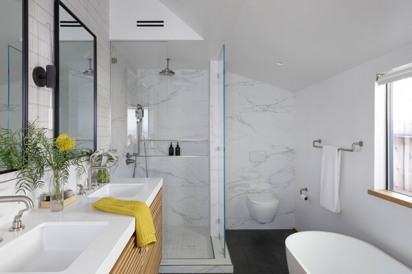 The wall of backsplash tile behind the sinks emphasizes the ceiling height.