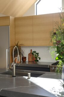 The faucet is by Brizo, and the sink is from Kräus. The backsplash is a handmade white ceramic tile that lends some organic irregularity to the scheme.