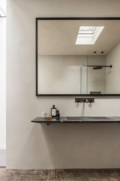 The sleek wall-hung sink is made of Black Marquina and complemented by the texture of the terracotta floor tiles. The clay wall coating has a waterproof finish in the bathrooms.