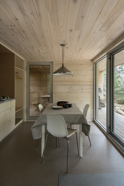 """Large sliding glass doors access the covered deck, where guests can barbeque. The lights run on solar-power. """"The lighting at night is warm,"""" says St-Laurent. """"It's really nice because when you're in the forest and the atmosphere is blue because of the water, then the cabin is like a lantern."""""""