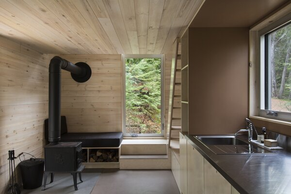 The wood stove heats the cabin efficiently in winter. The seating nook beside it doubles as wood storage.