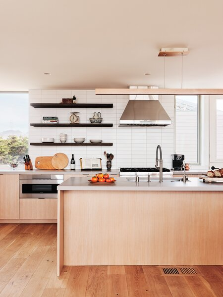 Windows stretch from the counter to the ceiling to maximize the view. The difference in ceiling height gives the kitchen a cozier feel.