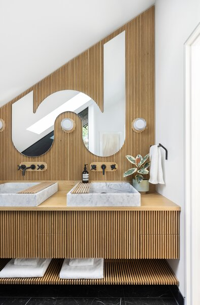 """Since the couple think of the addition as an """"extrusion,"""" they """"carried that theme to the rest of the house with the vertical fixtures on the stair and the vertical slats in the bathroom vanity,"""" says Jason. The marble sink basins are from Stone Forest. The custom shape of the mirror swirls around lights from Rich Willing and Brilliant. Faucets from Rejuvenation are mounted on white oak backplates inset into the slats."""