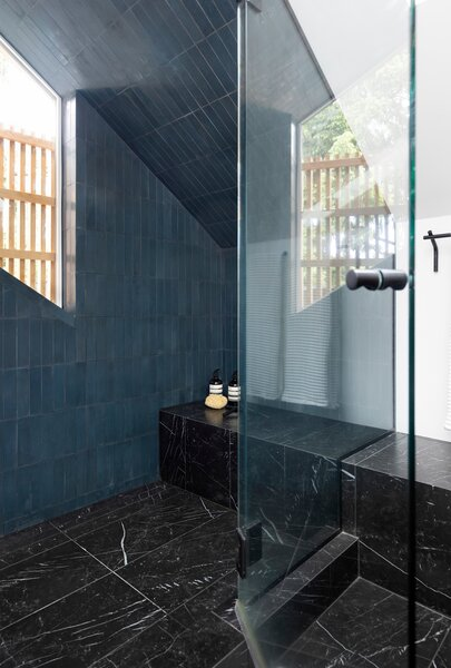 The shower has concrete tile from Zia Tile which was painstakingly cut to follow the angle of the ceiling. The exterior wood screen provides privacy over the windows while allowing light in.
